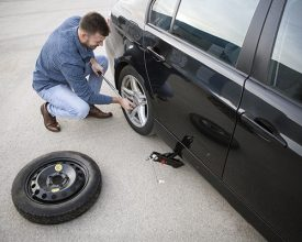 Man changing a flat tire on his car. About 25 years old, Caucasian male.