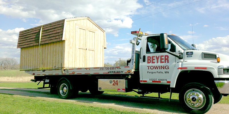 Beyer towing hauling shed on flatbed truck